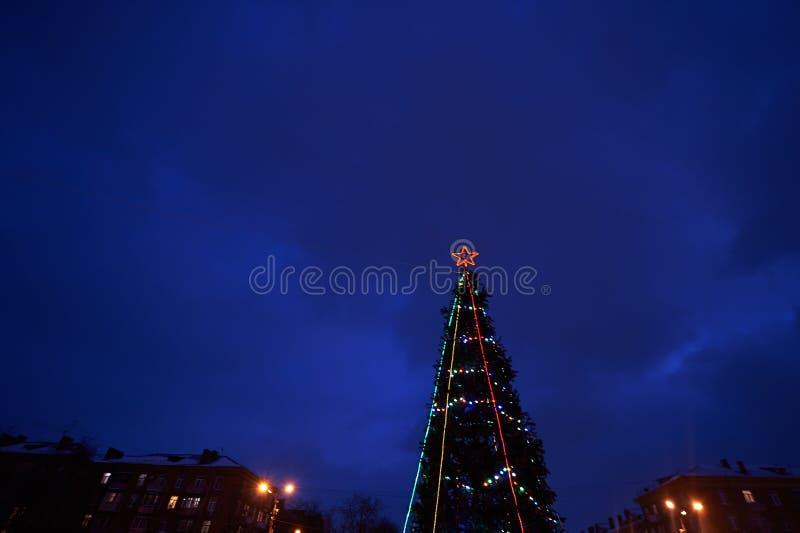 与一个红色星的装饰的圣诞树发光点燃反对深蓝天空 免版税库存照片