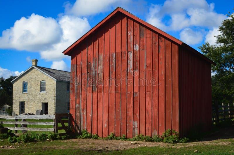 与一个红色谷仓大厦的老石大厦 库存照片