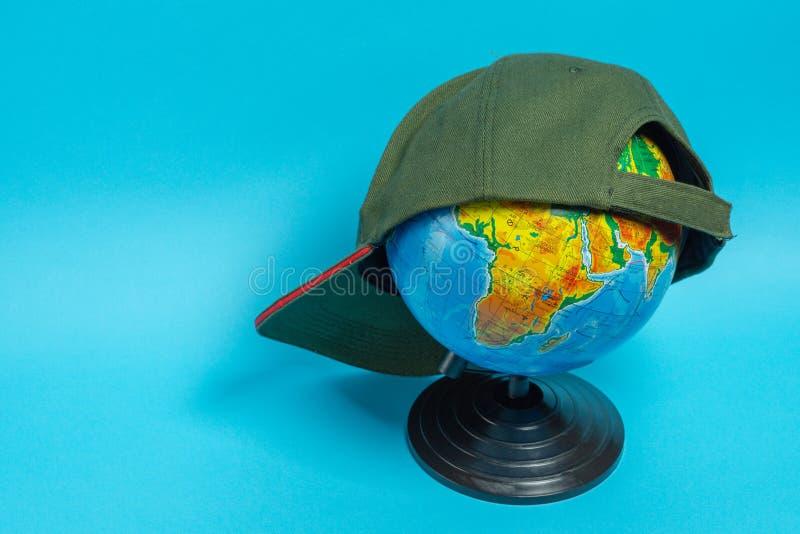 与一个绿色棒球帽的地球对此在蓝色背景 免版税库存图片