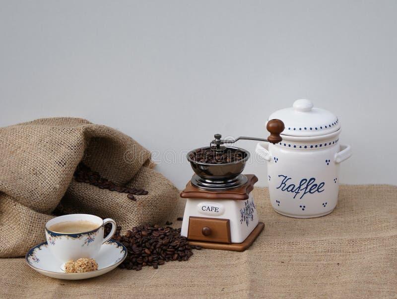 与一个老磨咖啡器的静物画,一杯咖啡和老瓷咖啡锡 免版税图库摄影