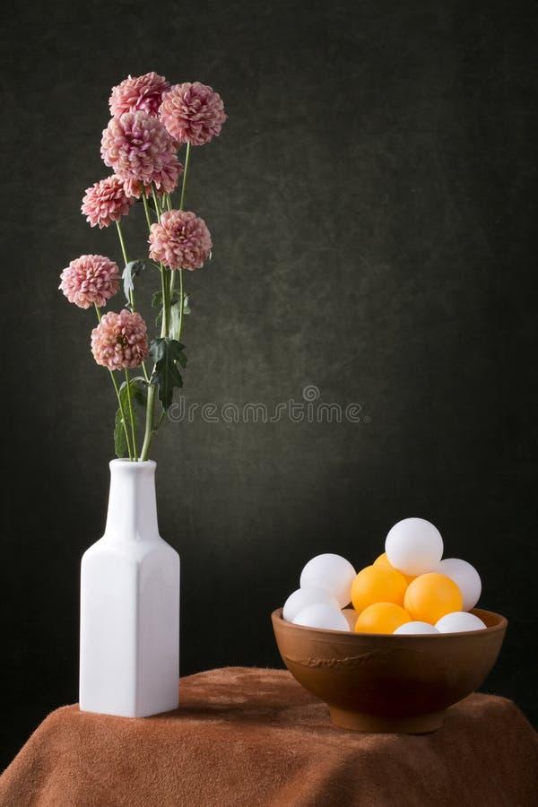 与一个花分支的静物画在有五颜六色的球的一个白色花瓶 免版税库存照片