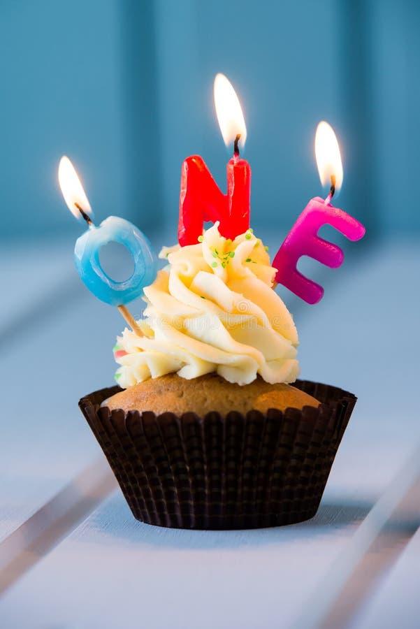 与一个蜡烛的杯形蛋糕1的-第一个生日 免版税库存图片
