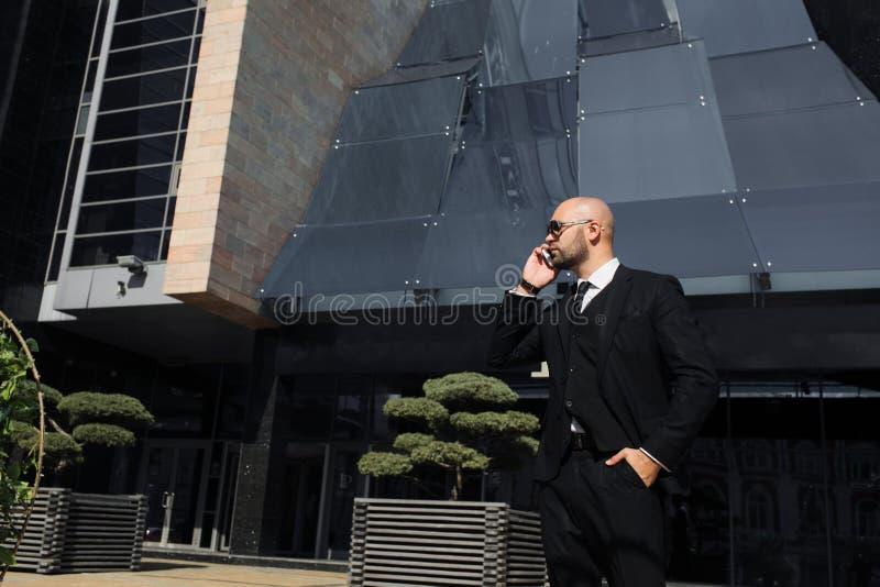 与一个袋子的商人在办公室附近谈话在电话 免版税库存照片
