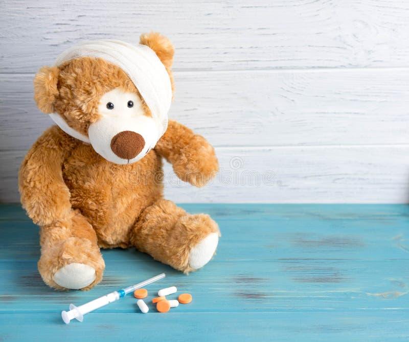 与一个被包扎的头的玩具熊倒带了 为横幅的依据与孩子相关健康  儿童健康 注射器 库存照片
