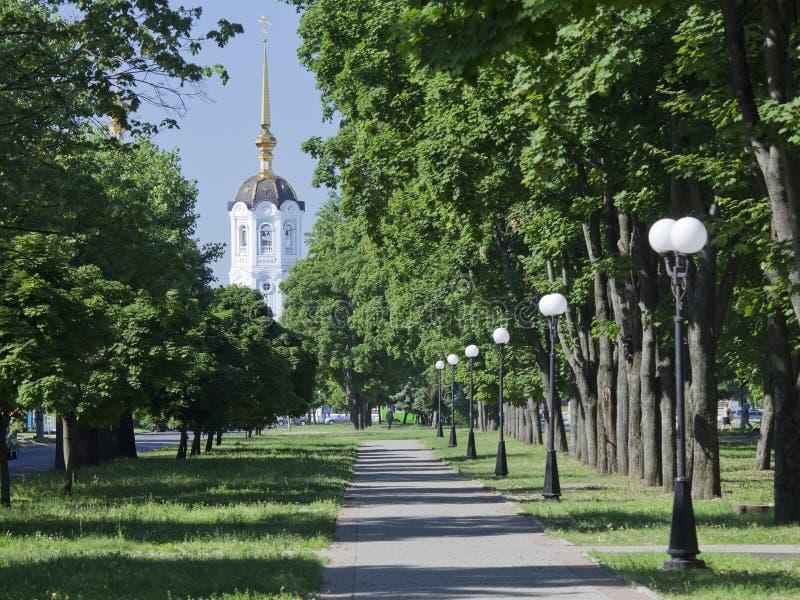 与一个被镀金的尖顶的白色钟楼在蓝天背景fram 库存图片