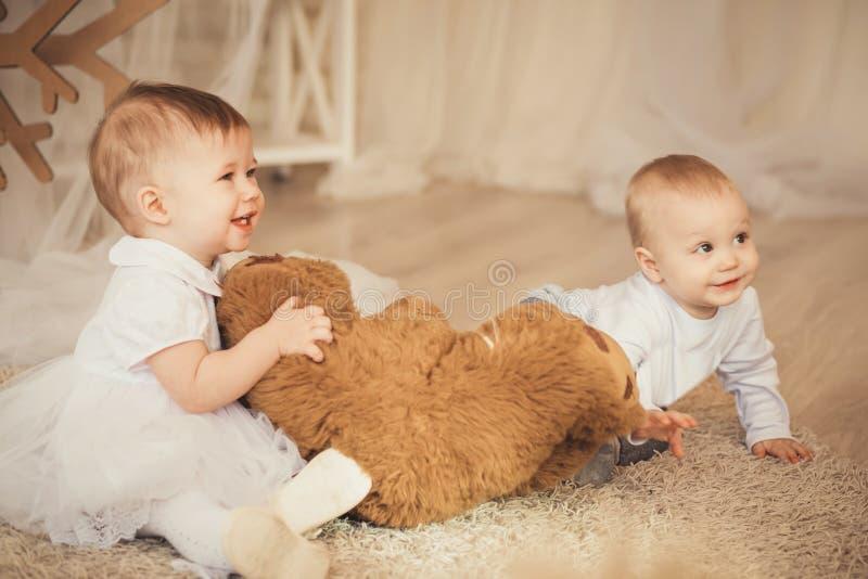 与一个软的棕色玩具熊的孩子在与圣诞节的内部 免版税库存照片