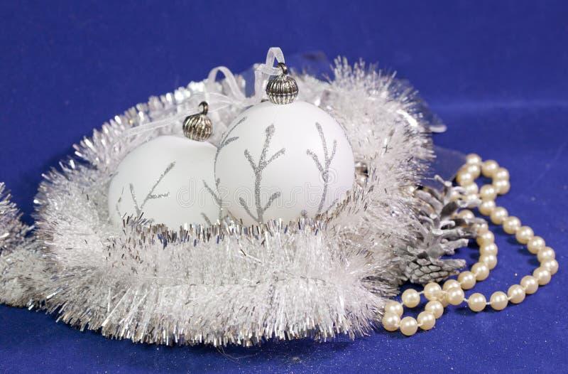 与一个银色样式、白色精采闪亮金属片、锥体和珍珠的美丽的白色玻璃新年` s球在蓝色背景成串珠状 库存照片