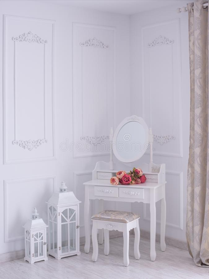 与一个镜子和花的梳妆台在屋子里 免版税库存照片