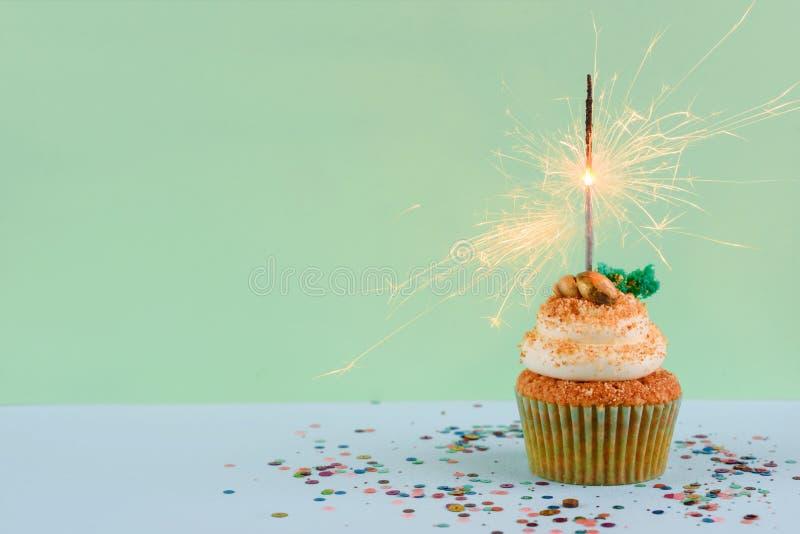 与一个闪烁发光物的生日杯形蛋糕在蓝色背景 免版税库存图片