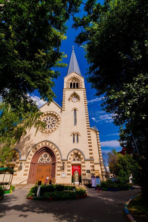 与一个高尖顶的宽容大教堂大教堂 反对天空蔚蓝的风景 在前景是树冠  免版税库存照片