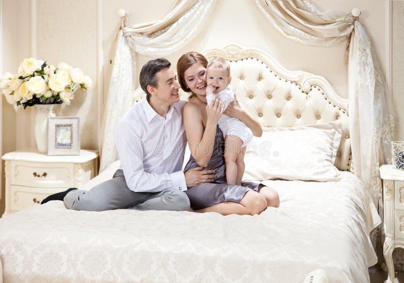 与一个婴孩的年轻愉快的家庭在床上 免版税库存图片