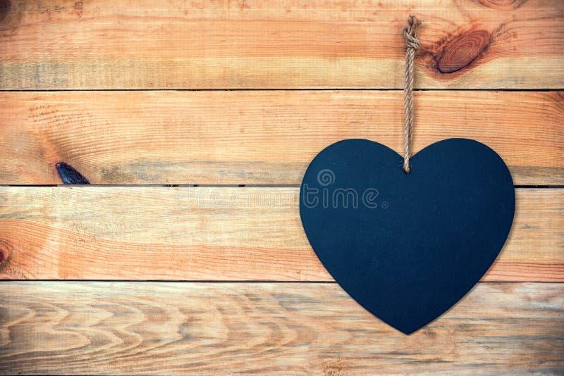 与一个黑板的木板条以心脏,爱与拷贝空间的贺卡背景的形式 免版税图库摄影