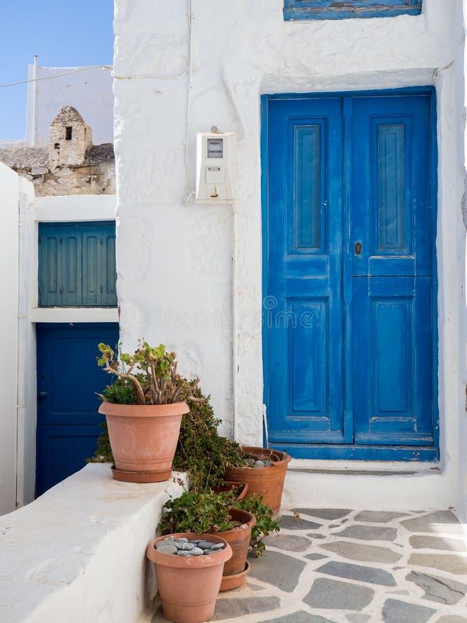 与一些泥罐的一个小传统蓝色门在前面 免版税库存照片