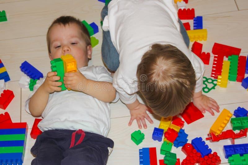 与一位多色设计师的儿童游戏 一个小男孩和女孩在一位多彩多姿的设计师,难题中说谎 在玩具中的孩子 免版税库存照片