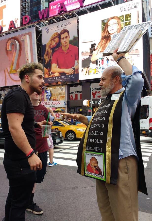 与一位宗教传教者的交锋在时代广场, NYC, NY,美国 免版税库存照片