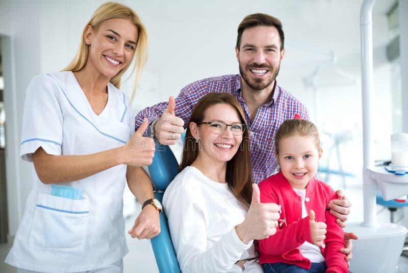 与一位微笑的年轻女性牙医的满意的家庭 免版税库存图片