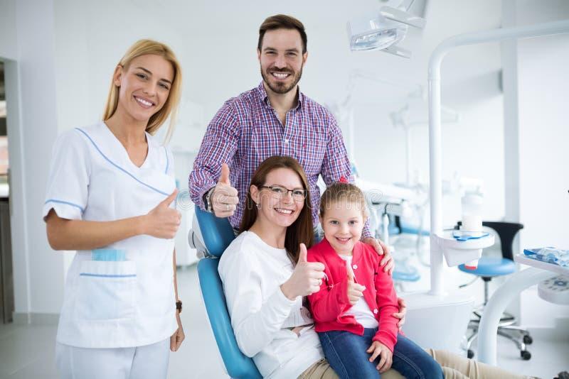 与一位微笑的年轻牙医的愉快的家庭 免版税库存图片