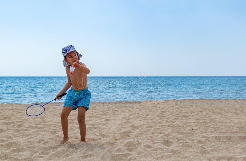 与一副羽毛球拍和一shuttlecock的儿童游戏在海滩 免版税图库摄影