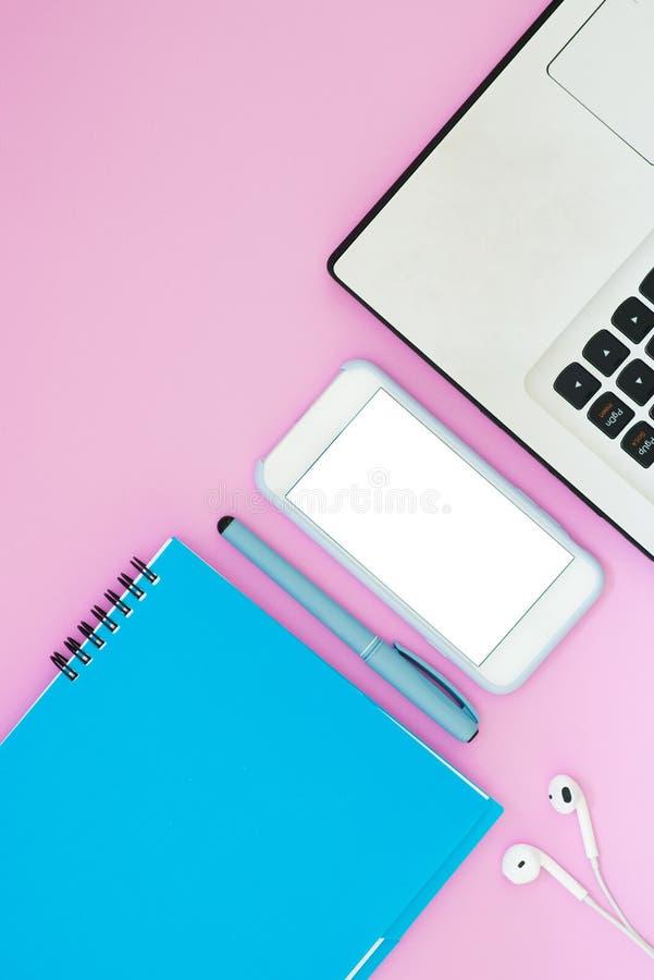 与一副膝上型计算机、电话、笔记薄和耳机的布局在桃红色背景 安置文本 工作的平的位置事 免版税库存照片
