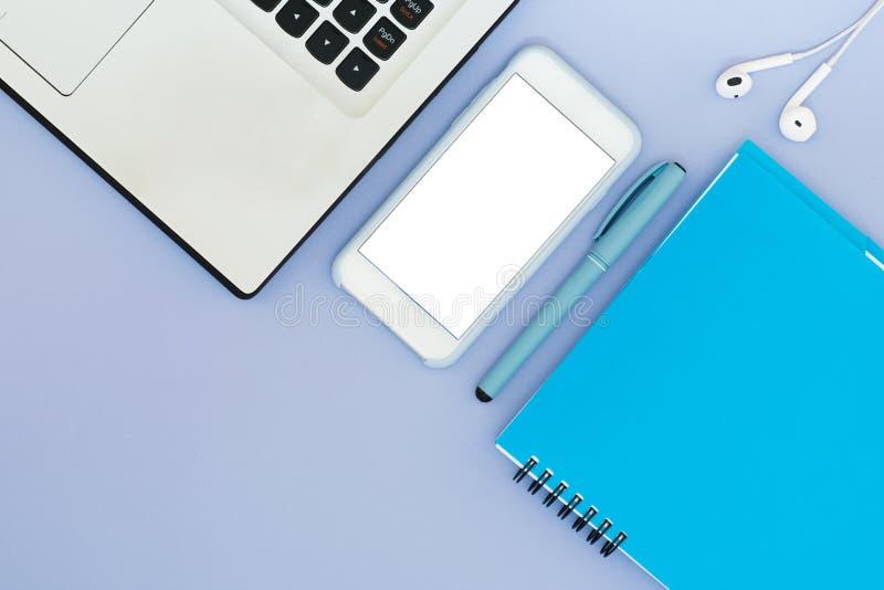 与一副膝上型计算机、电话、笔记薄和耳机的布局在蓝色背景 安置文本 平的位置桌面用工具加工布局 免版税库存照片