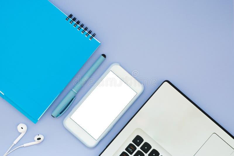 与一副膝上型计算机、电话、笔记薄和耳机的布局在蓝色背景 安置文本 平的位置桌面用工具加工布局 免版税图库摄影
