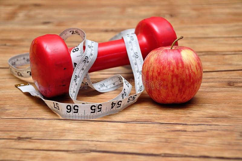 与一卷测量的磁带和苹果的一个红色哑铃 库存图片