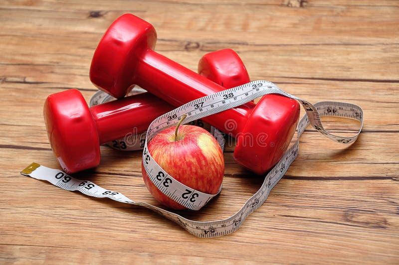 与一卷测量的磁带和苹果的红色哑铃 库存图片