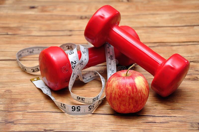 与一卷测量的磁带和苹果的红色哑铃 免版税库存照片