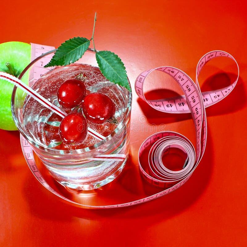 与一卷测量的磁带的一个绿色苹果 一个可口家做了饮料用在玻璃的新鲜的莓果 库存照片