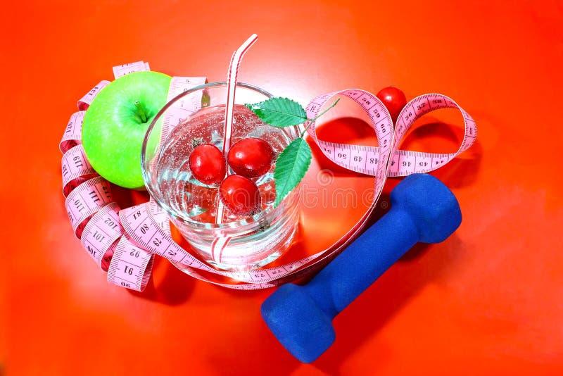 与一卷测量的磁带的一个绿色苹果 一个可口家做了饮料用在玻璃的新鲜的莓果 库存图片