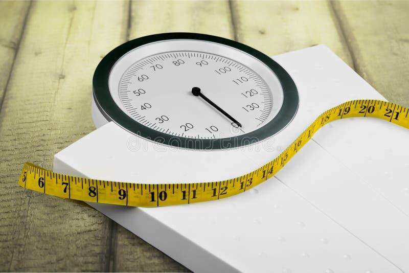 与一卷测量的磁带的体重计,特写镜头 免版税图库摄影