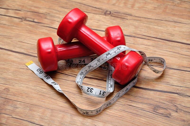 与一卷测量的磁带的红色哑铃 库存照片