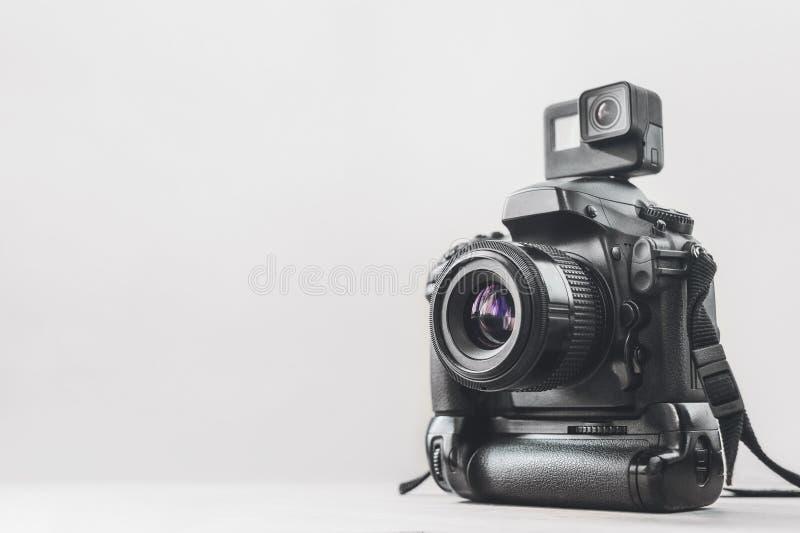 与一台专业照相机的行动照相机在白色背景 免版税库存图片