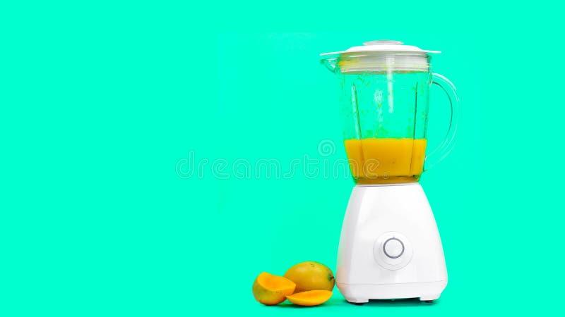 与一台搅拌器的芒果汁,在绿色背景 库存照片