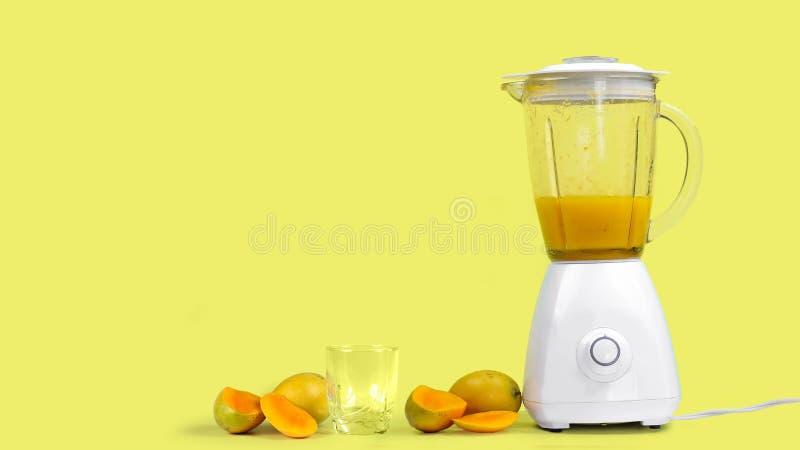 与一台搅拌器的芒果汁,在黄色背景 免版税库存图片
