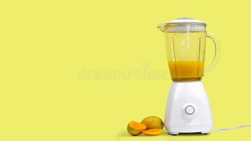 与一台搅拌器的芒果汁,在黄色背景 免版税库存照片
