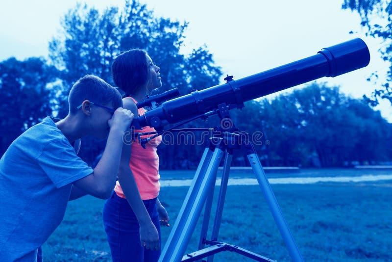 与一台望远镜的青少年在晚上 看与兴趣的孩子在天空上 免版税库存图片