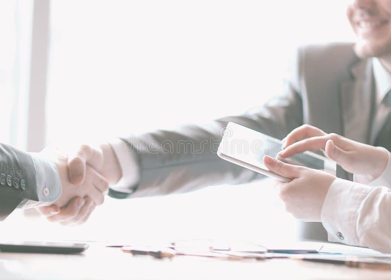 与一台片剂计算机的商人在商务伙伴握手的背景  图库摄影