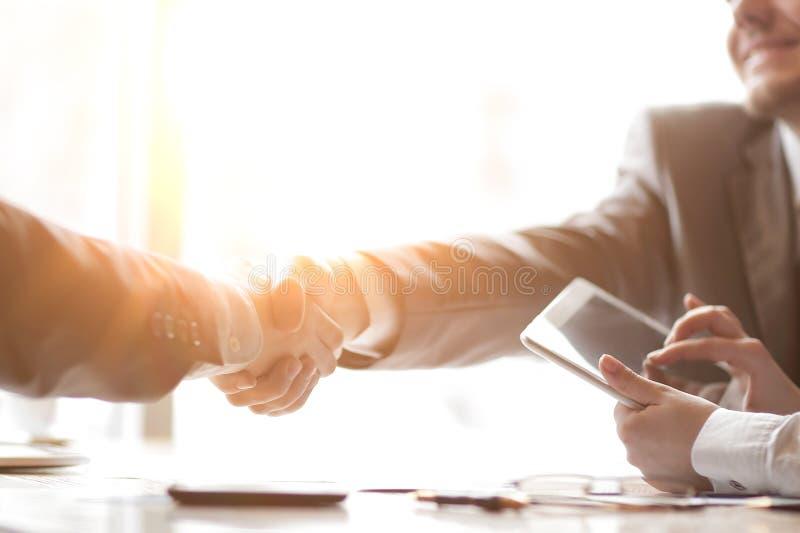 与一台片剂计算机的商人在商务伙伴握手的背景  免版税库存图片