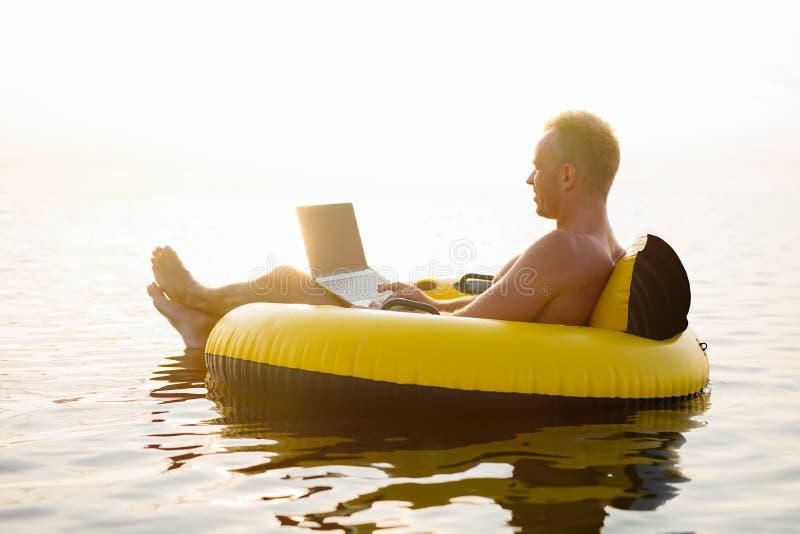 与一台膝上型计算机的商人在可膨胀的圆环在水中在日落 免版税图库摄影