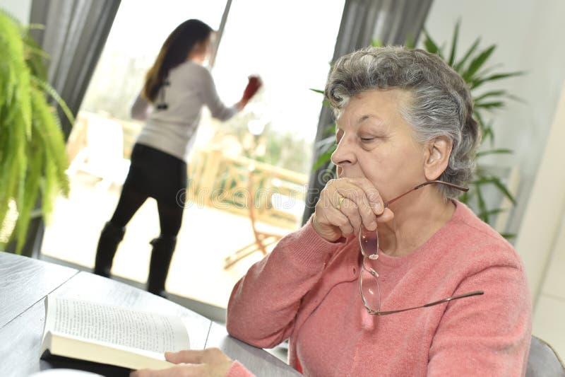 读与一名家庭护工的年长妇女一本书在背景中 免版税图库摄影