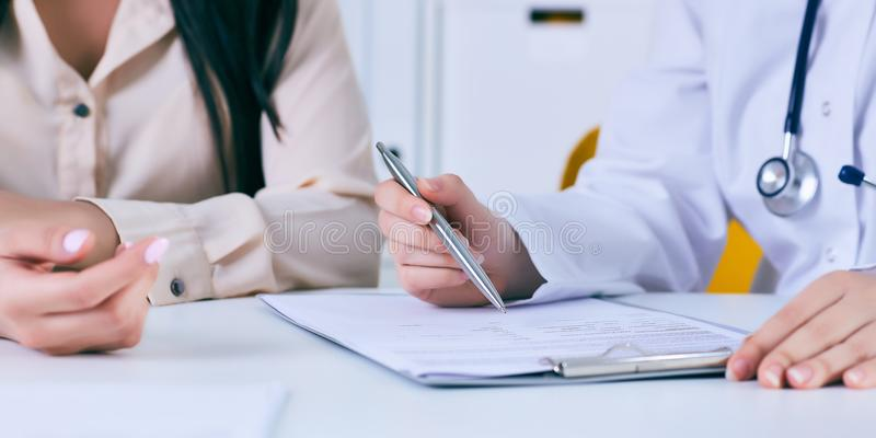 与一名患者的女性医生会谈在办公室,她给一张处方妇女 移交桌 免版税库存图片
