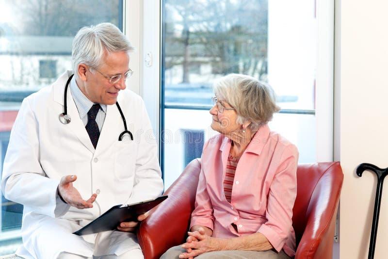 经与一名资深患者磋商的男性医生 库存照片