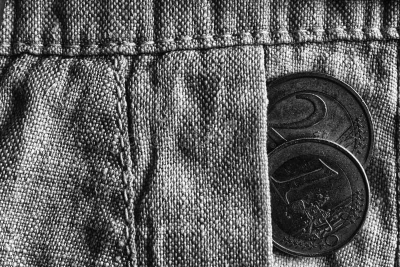 与一和两在破旧的亚麻布裤子的口袋,单色射击的欧元的衡量单位的欧洲硬币 免版税库存图片