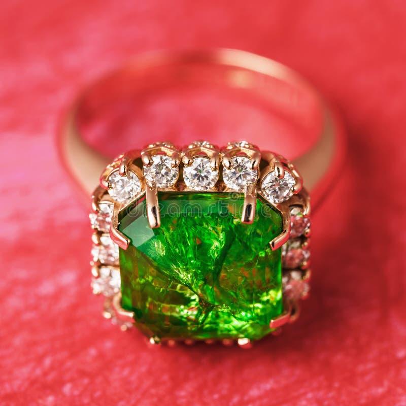 与一块大绿宝石的金黄圆环和从小立方体氧化锆的一条道路在红色抽象背景 免版税库存照片