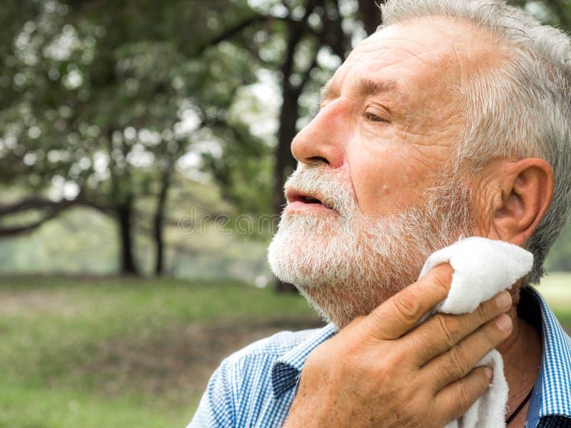 与一块毛巾的老人疲乏的抹的汗水在公园,医疗保健概念 免版税库存图片