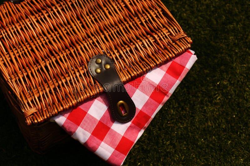 与一块红色和白色方格花布布料的柳条野餐篮子在草 免版税图库摄影