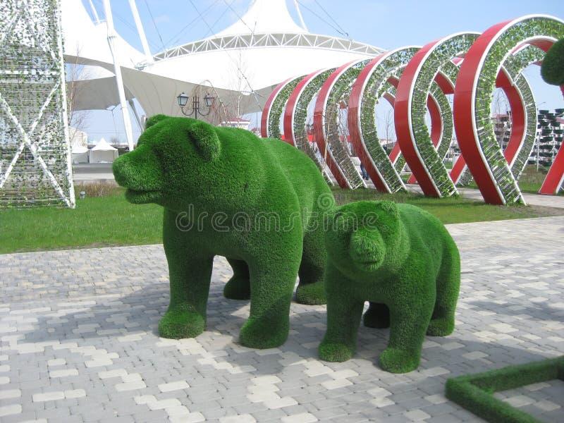 与一头小熊的绿色雕塑熊 修剪的花园绿的艺术 负担与一头小熊在格罗兹尼中央公园  库存图片