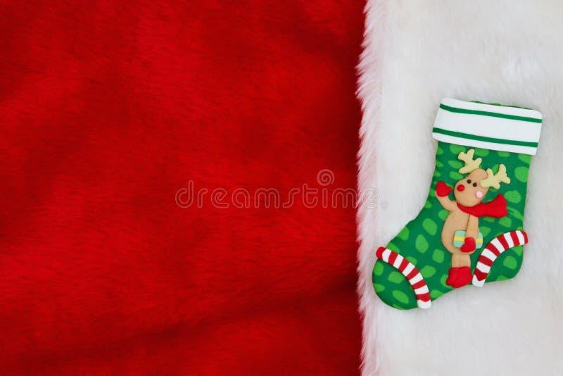 与一头驯鹿的圣诞节长袜在红色和白色豪华的织地不很细织品背景 免版税图库摄影