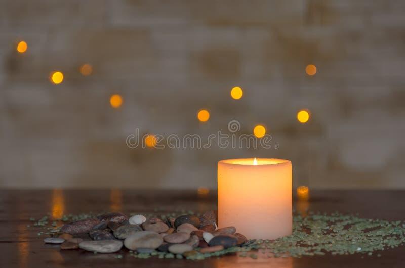 与一好的模糊的轻的bokeh的喜怒无常的烛光 为温泉完善 免版税库存照片